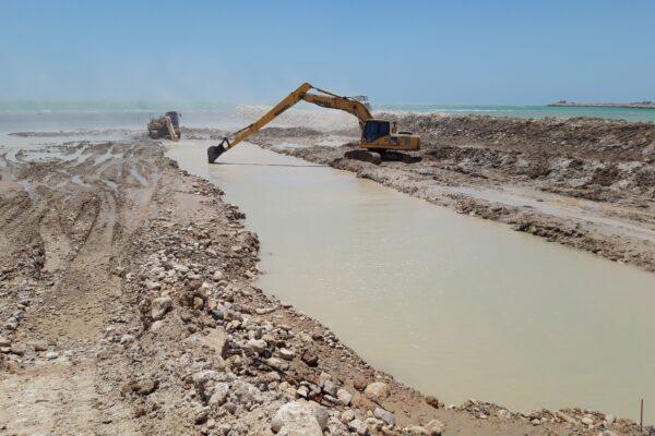 لایروبی ابتدای مسیر دریایی در زمان جزر با استفاده از بیل مکانیکی جهت اتصال دریا و خشکی
